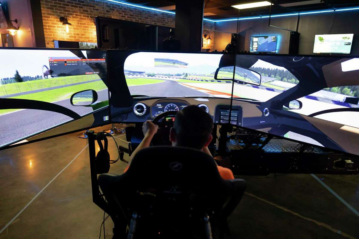 Mike McLennan, manager of Emergent VR Encounter, competes with colleague, Joel Chan, during a virtual realty car race, Tuesday, March 30, 2021, in Spring. The facility opened in 2018 and offers a variety of virtual reality experiences such as golfing, racing and more.