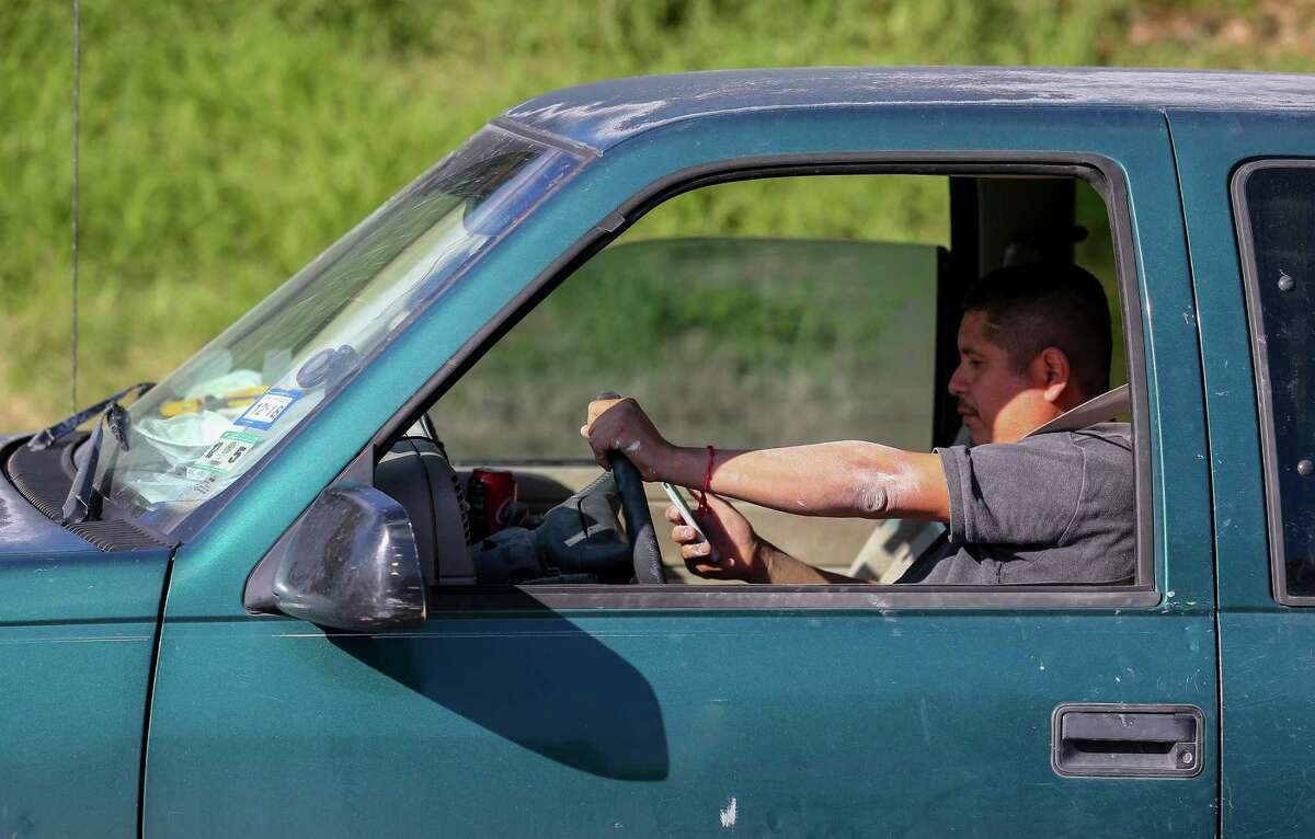 A motorist uses a cell phone while driving on the highway.