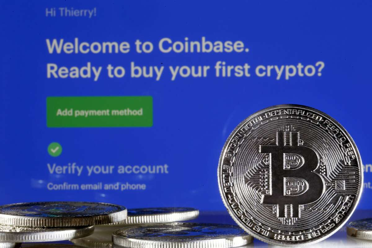 PARIS, FRANCE - FEBRUARY 26: In this photo illustration, a visual representation of the digital Cryptocurrency, Bitcoin is displayed in front of the Coinbase cryptocurrency exchange website on February 26, 2021 in Paris, France. Cryptocurrency trading platform Coinbase has filed for registration with the SEC on Thursday for an IPO via direct listing on the Nasdaq and will likely be the largest IPO of the year. Coinbase reported $ 1.28 billion in revenue in 2020 (+ 140% year on year), for net profit of $ 320 million. (Photo illustration by Chesnot/Getty Images)