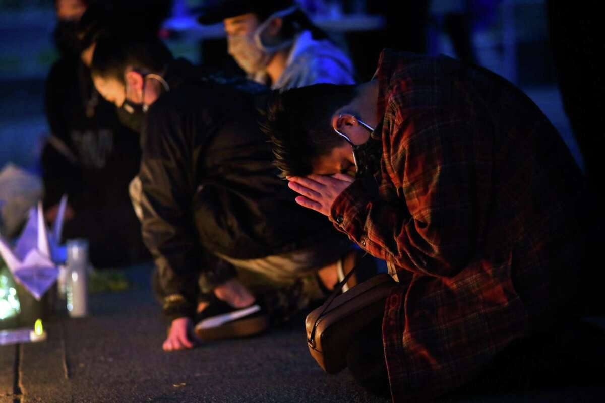 Kiara Konishi (they/them) of Oakland prays in front of an altar as hundreds gather for the
