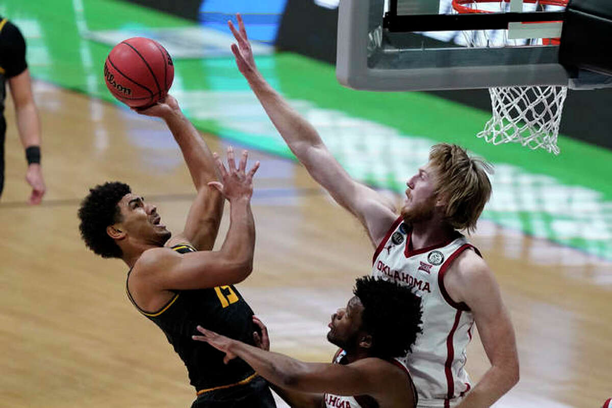 Missouri guard Mark Smith, left, shoots over Oklahoma guard Elijah Harkless, center, and forward Brady Manek, right, during the second half of a first-round game in the NCAA men's college basketball tournament at Lucas Oil Stadium, Saturday, March 20, 2021, in Indianapolis.