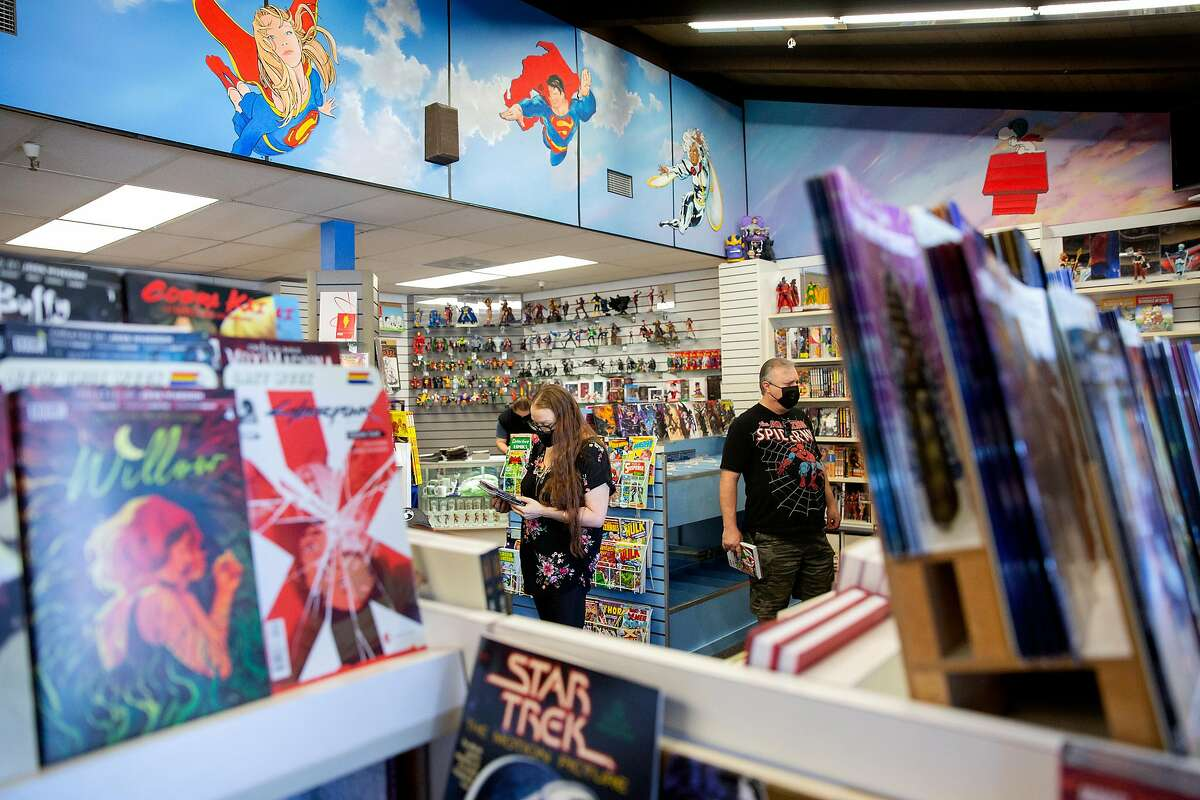 Customers peruse the aisles looking over newly released comic books at Flying Colors Comic Books in Concord in October. California is preparing to retire its colored tier system as counties are moving toward meeting requirements for reopening.