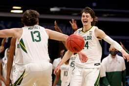 INDIANAPOLIS, INDIANA - MARCH 21: Jackson Moffatt #13 of the Baylor Bears and Matthew Mayer #24 of the Baylor Bears react after their 76-63 win over the Wisconsin Badgers in the second round game of the 2021 NCAA Men's Basketball Tournament at Hinkle Fieldhouse on March 21, 2021 in Indianapolis, Indiana. (Photo by Gregory Shamus/Getty Images)