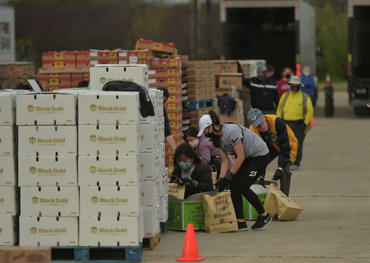 Volunteers pack bags during a San Antonio Food Bank mega distribution Friday morning at Brooks. Broadway Bank sponsored the event and donated $50,000.