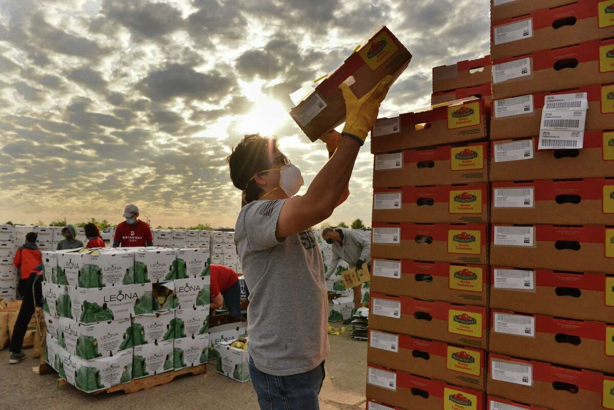 Juan Carlos Gonzalez stacks boxes of tomatoes during a San Antonio Food Bank mega distribution Friday morning at Brooks. Broadway Bank sponsored the event and donated $50,000.