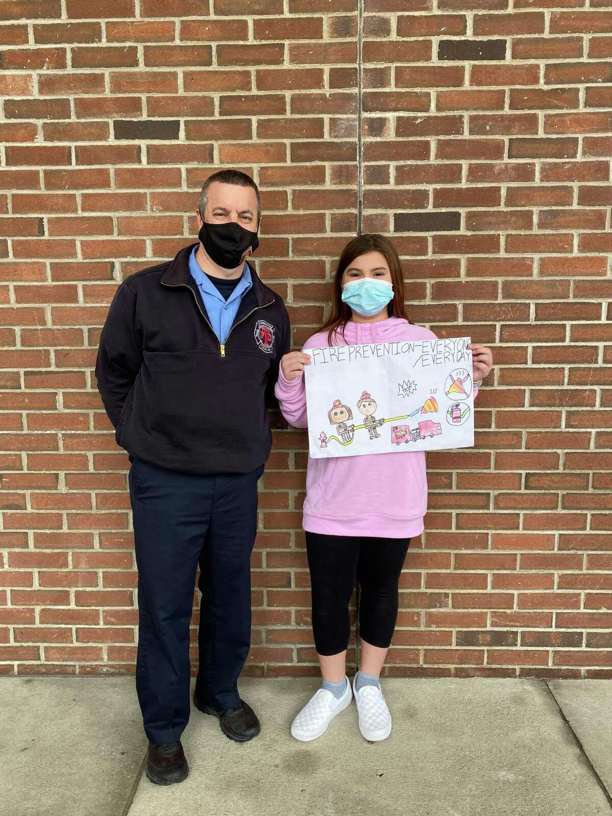 Jarred Howe, Torrington deputy fire marshal, stands with Mia Diaz, Forbes School fourth grader, winner of the 2021 fire prevention poster contest.