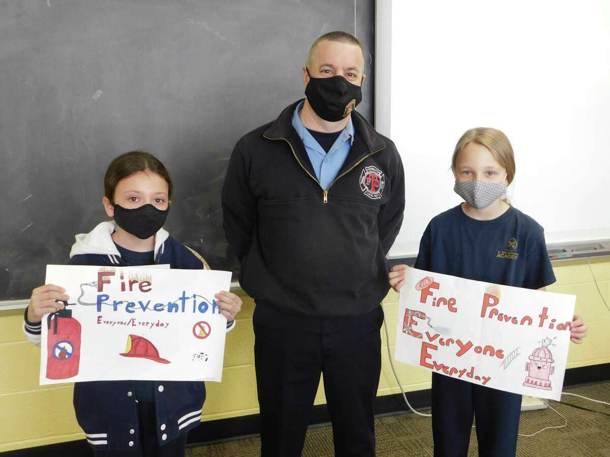 Jarred Howe, Torrington deputy fire marshal, stands with Isabella O'Brien, left, and Alexandra Mazzarelli, fifth-grade students at St. John Paul the Great Academy, winners of the 2021 fire prevention poster contest.