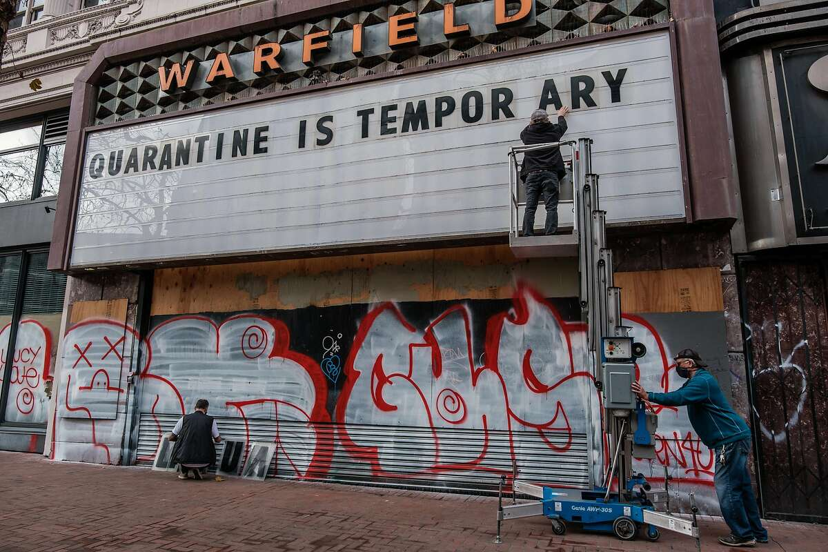 Tom Hazlett, Matt Albrecht and Christian Lewis change the marquee at the Warfield Theatre in January.