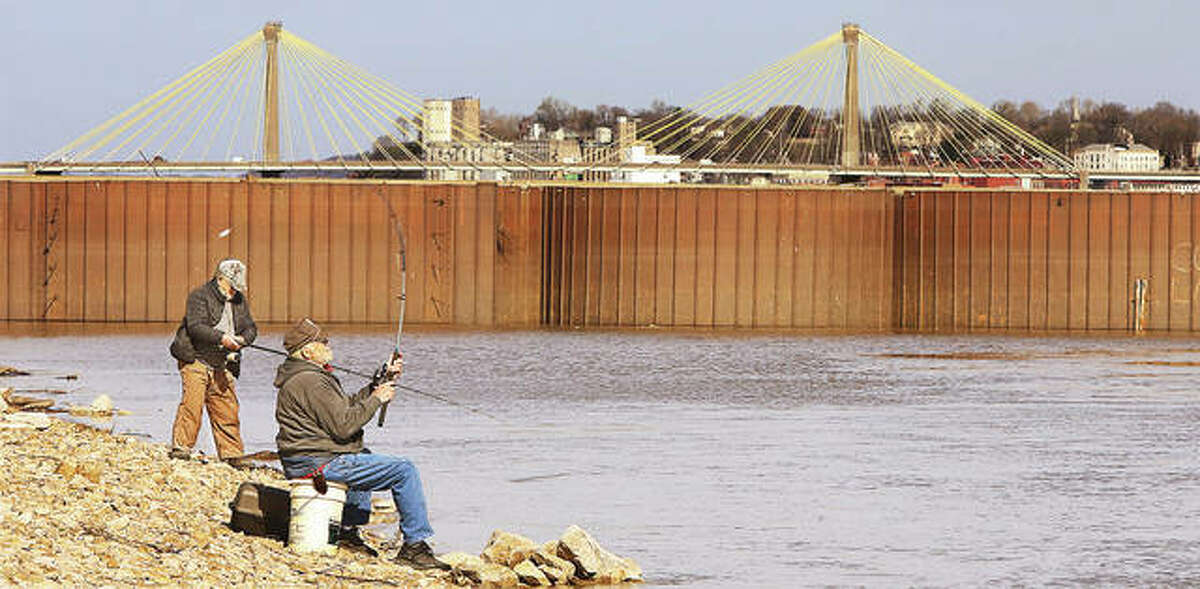Two men take advantage of Tuesday's sunshine to try their hand at fishing next to the Melvin Price Locks and Dam 26.