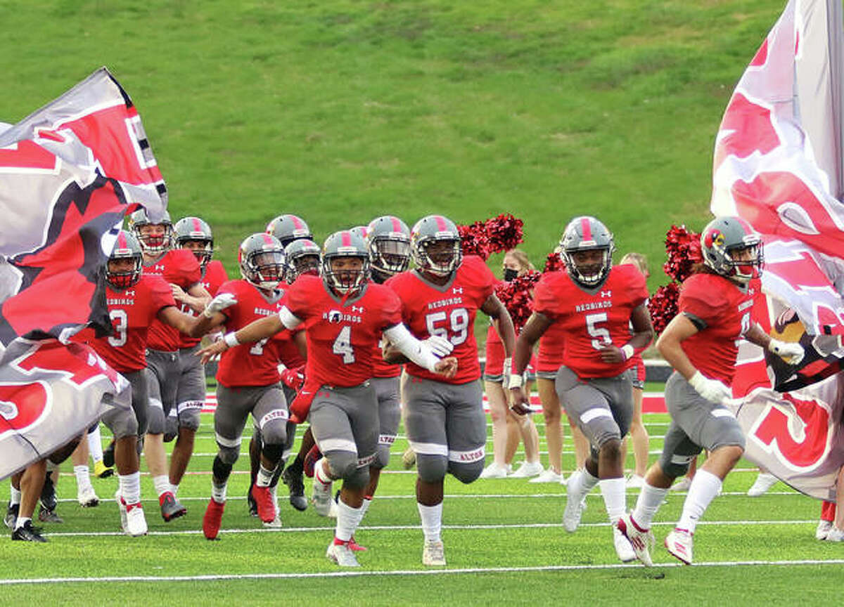 Alton's Keith Gilchrese (4), Ihzel Brown (59), Tim Johnson (5) and Damien Jones (right) lead the Redbirds through the banner before Saturday's football game against Champaign Central at Public School Stadium in Alton.