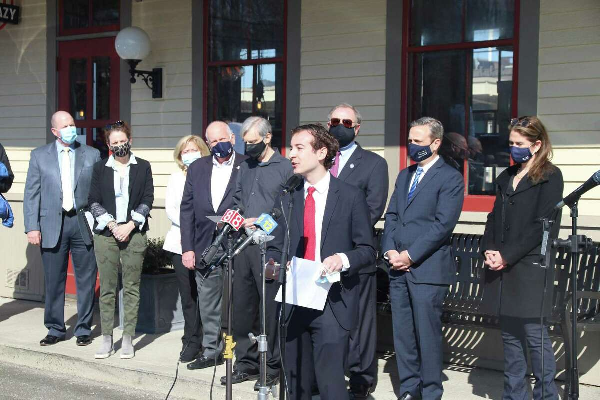 State Sen. Will Haskell, front, speaks at a recent rally at the Westport Train Station with fellow electric vehicle supporters behind him.