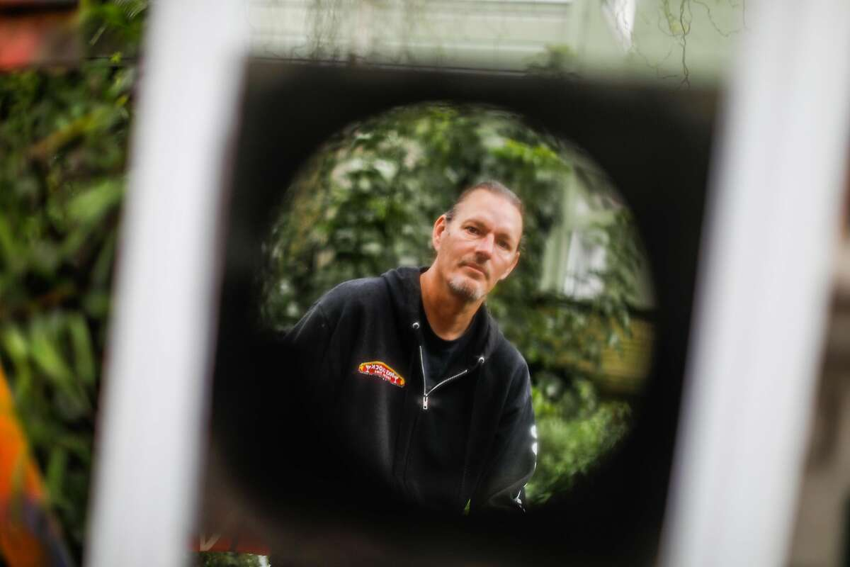 Frank Jaworski, shown reflected in the mirror in his yard, reported almost $3,500 of unemployment benefits stolen from his Bank of America EDD debit card.
