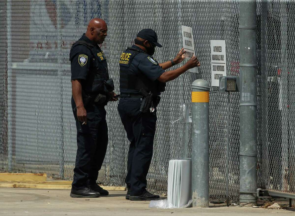 """A U.S. Department of Homeland Security Federal Protective Service officer places an """"authorized individuals only"""" sign on the fence surrounding the National Association of Christian Churches warehouse, on Friday, April 2, 2021, in Houston. Five hundred unaccompanied migrant teenage girls are expected to be housed at this facility."""