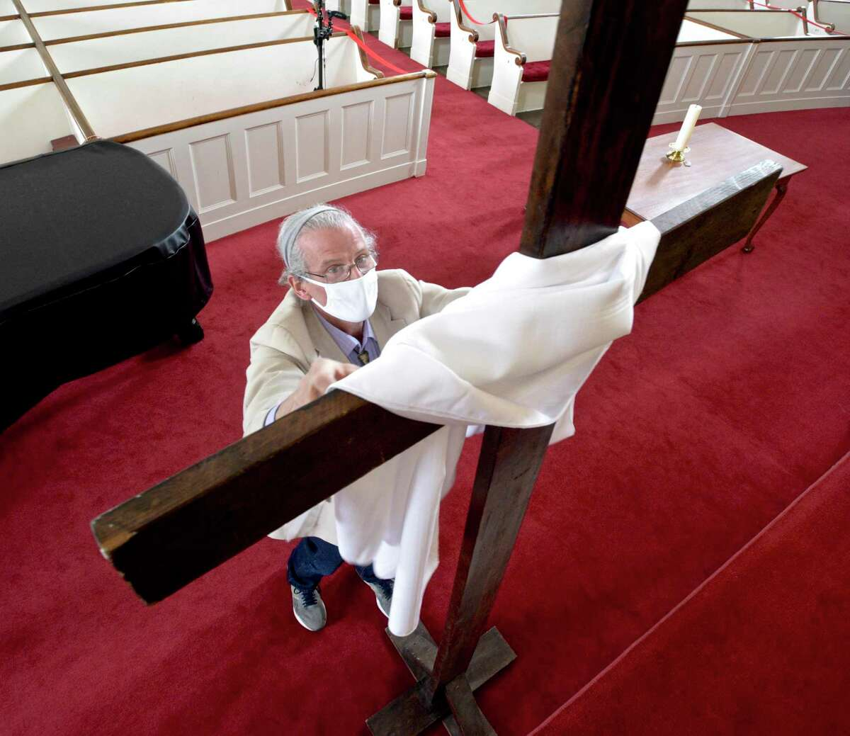 Gregory Pings, of Danbury, replaces a black cloth hung on the cross with a white one in the First Congregational Church, on Deer Hill Avenue. The church had started preparing for Easter. The sanctuary of the church will be open on Easter for the first time since last fall. Friday, April 2, 2021, in Danbury, Conn.