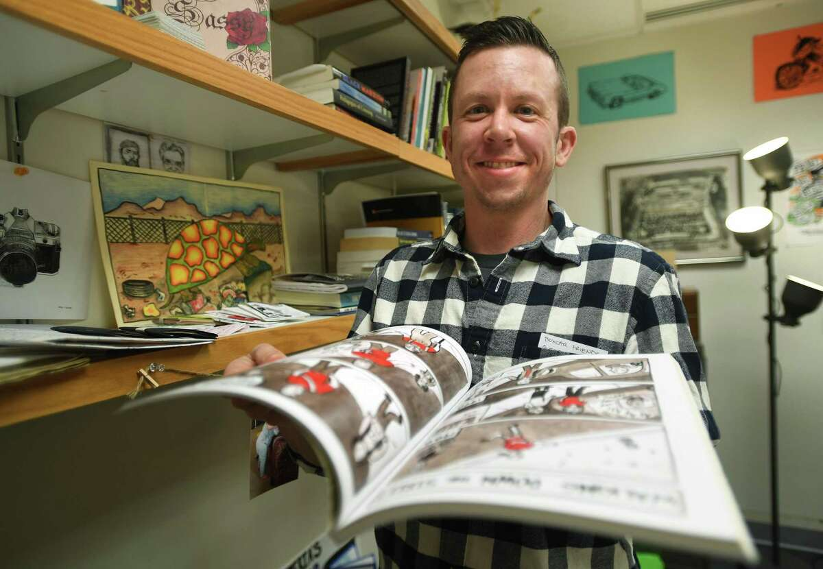 KC Councilor, an associate professor of communications, helped in discovering his identity as a transgender man through cartoons and comics, at Southern Connecticut State University in New Haven April 1, 2021. He holds his self-published book,