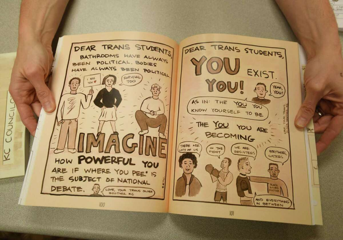 """KC Councilor, an associate professor of communications, helped in discovering his identity as a transgender man through cartoons and comics, at Southern Connecticut State University in New Haven Thursday, April 1, 2021. He holds his self-published book, """"Between You and Me - Transitional Comics."""""""