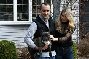 Former New York City residents Jesse Leder and Tashina Zamlowski stand outside their new home with dog, Amelia Peppercorn, on Friday, April 2, 2021, in Saratoga, N.Y. (Will Waldron/Times Union)