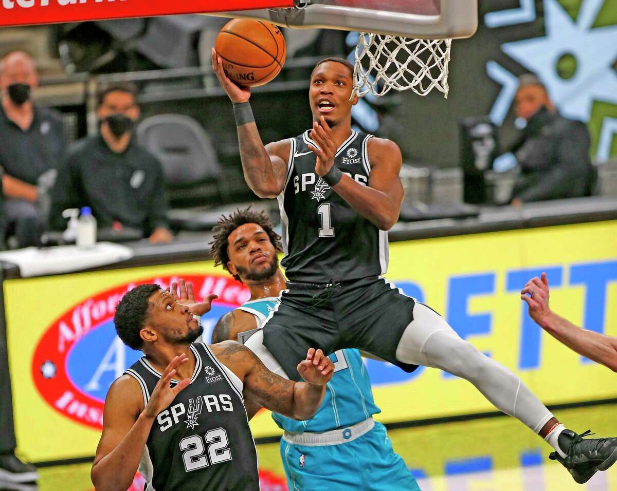 Lonnie Walker of the Spurs shoots and scores against the Charlotte Hornets as teammate Rudy Gay looks on at AT&T Center on March 22, 2021.