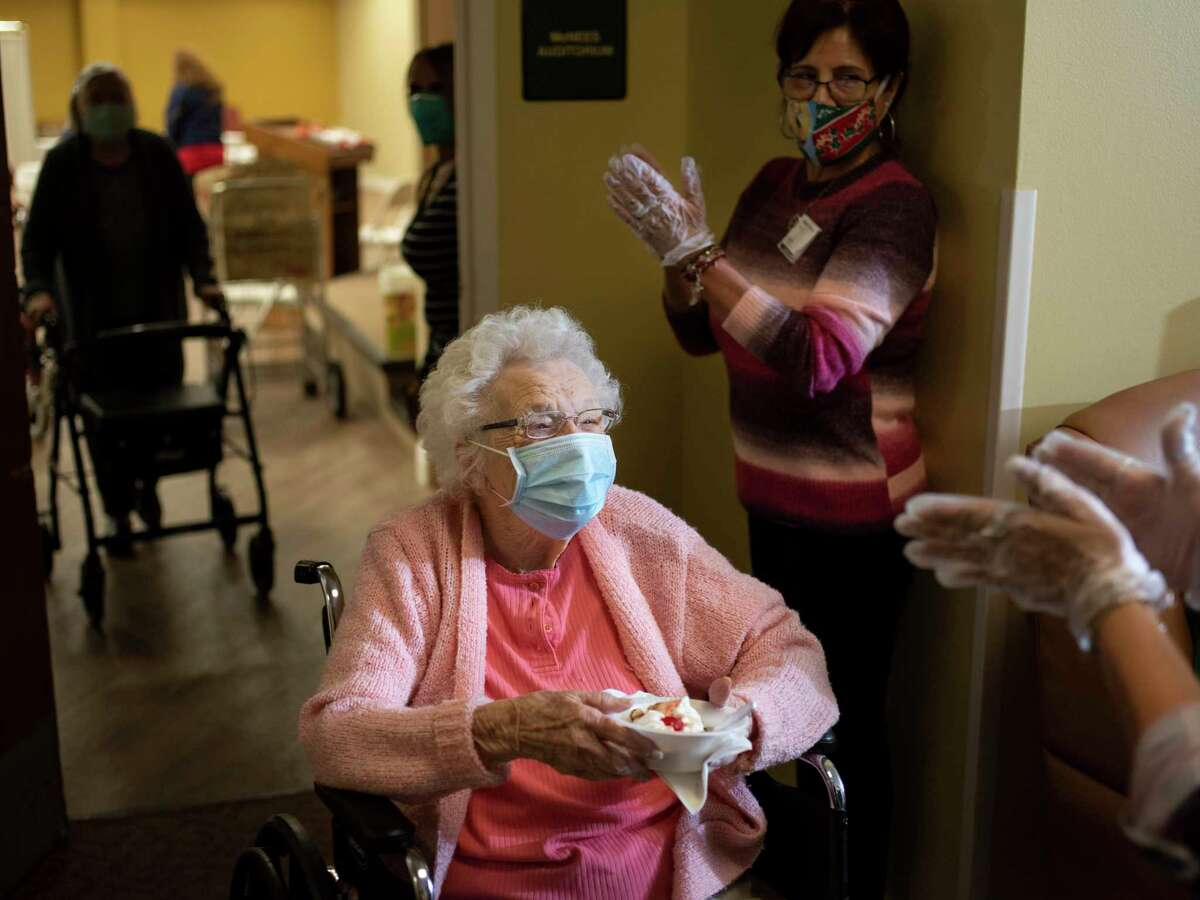 A resident at Morningside Ministries Assisted Living Facility receives a banana split and a round of applause after getting a COVID vaccine in December. Visits to nursing homes have resumed, and with that comes a lot of joy, but also risk.