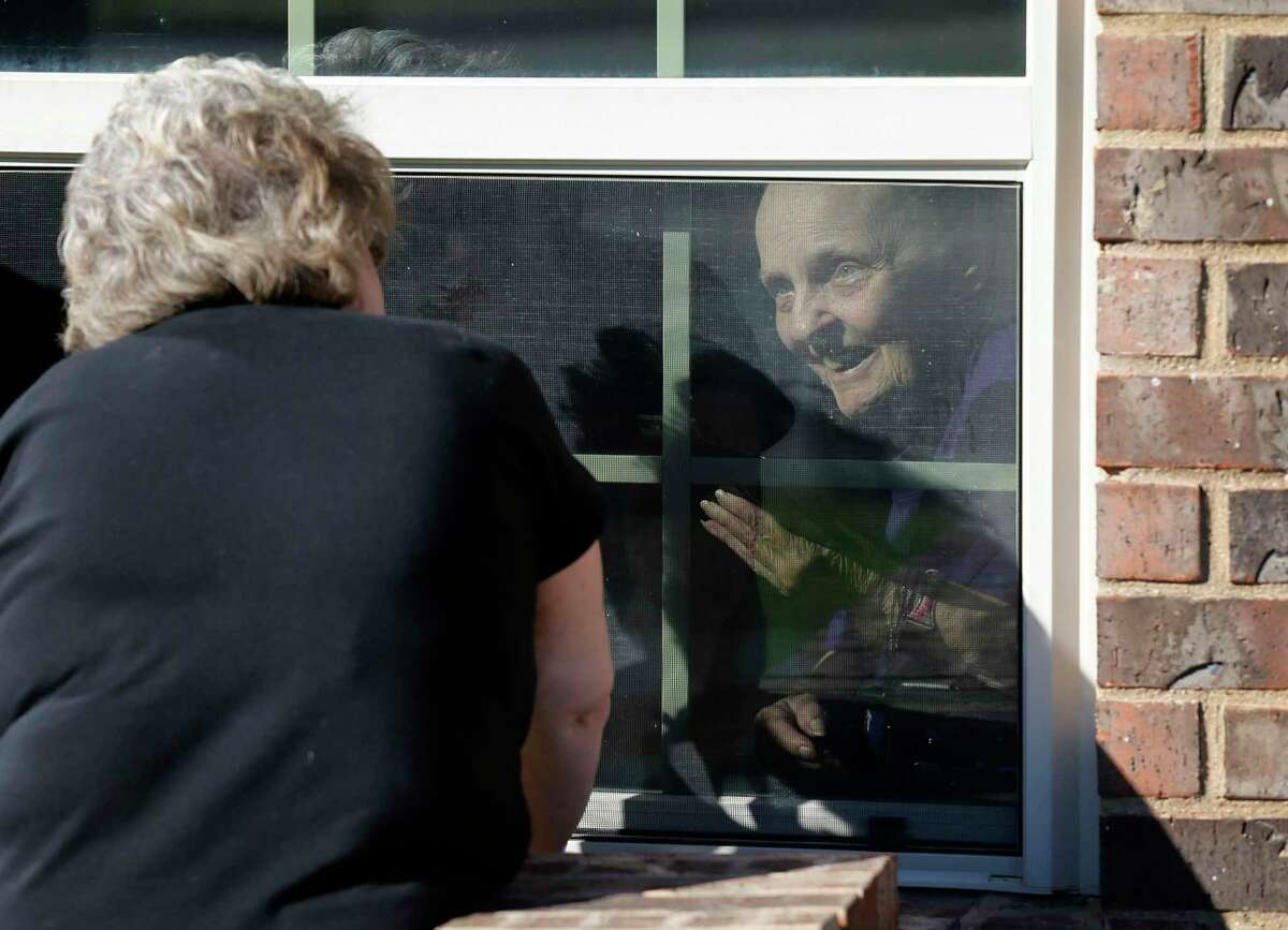 A woman visits her mother at a nursing home in Mansfield in March of 2020. The return of nursing home visits has brought joy, and some concern about health and safety.