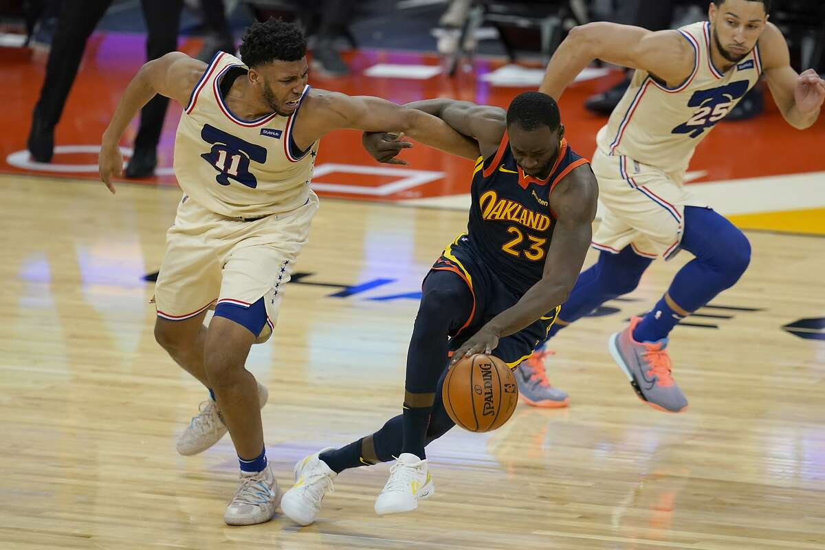 Golden State Warriors forward Draymond Green (23) is defended by Philadelphia 76ers center Tony Bradley (11) during an NBA basketball game in San Francisco, Tuesday, March 23, 2021. (AP Photo/Jeff Chiu)