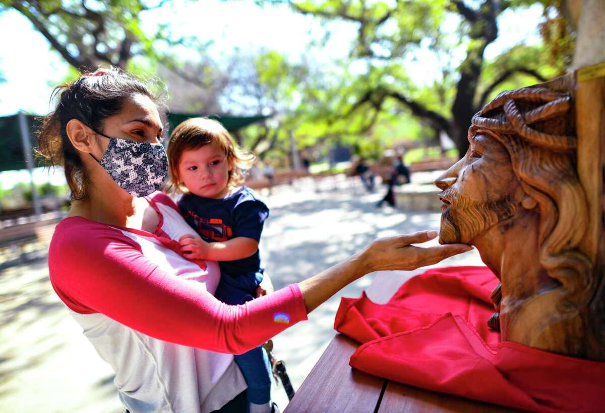 Mary Sanchez holds her son, Nehemiah, as she gently touches a wood carving of the face of Jesus Christ at Our Lady of Lourdes Grotto on Friday, April 2, 2021. The traditional walking of each of the Stations of the Cross was not done this year as a safety precaution because of the coronavirus.