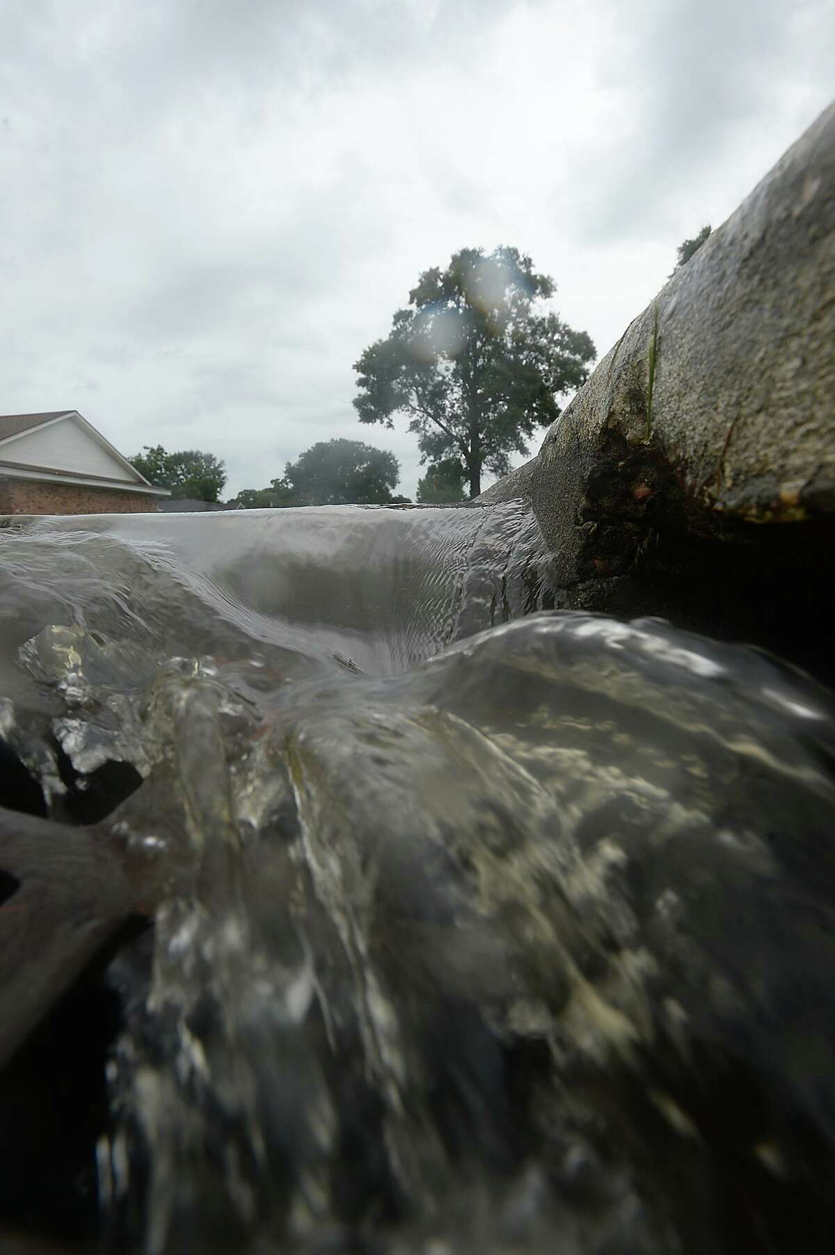 Water pours into a storm drain on 31st Street in Nederland as spotty bursts of rain move through the area Saturday, briefly accumulating on streets near Nederland Avenue, which is prone to flooding in heavy rainfalls. Heavier rains and wind from the outer bands of Hurricane Harvey, which was downgraded to a tropical storm, are expected to impact the Southeast Texas region within the coming days, increasing the risk for severe flooding. Photo taken Saturday, August 26, 2017 Kim Brent/The Enterprise