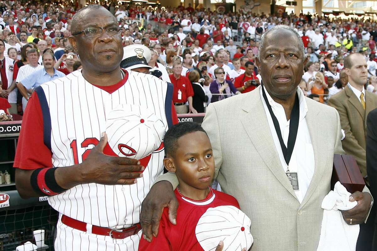 Cincinnati Reds manager Dusty Baker, left, stands with his son Darren Baker, center, and baseball great Hank Aaron, right, as the national anthem plays during the Civil Rights Game ceremony before a game between the Chicago White Sox and the Cincinnati Reds at Great American Ball Park, Saturday, June 20, 2009, in Cincinnati. (AP Photo/David Kohl)