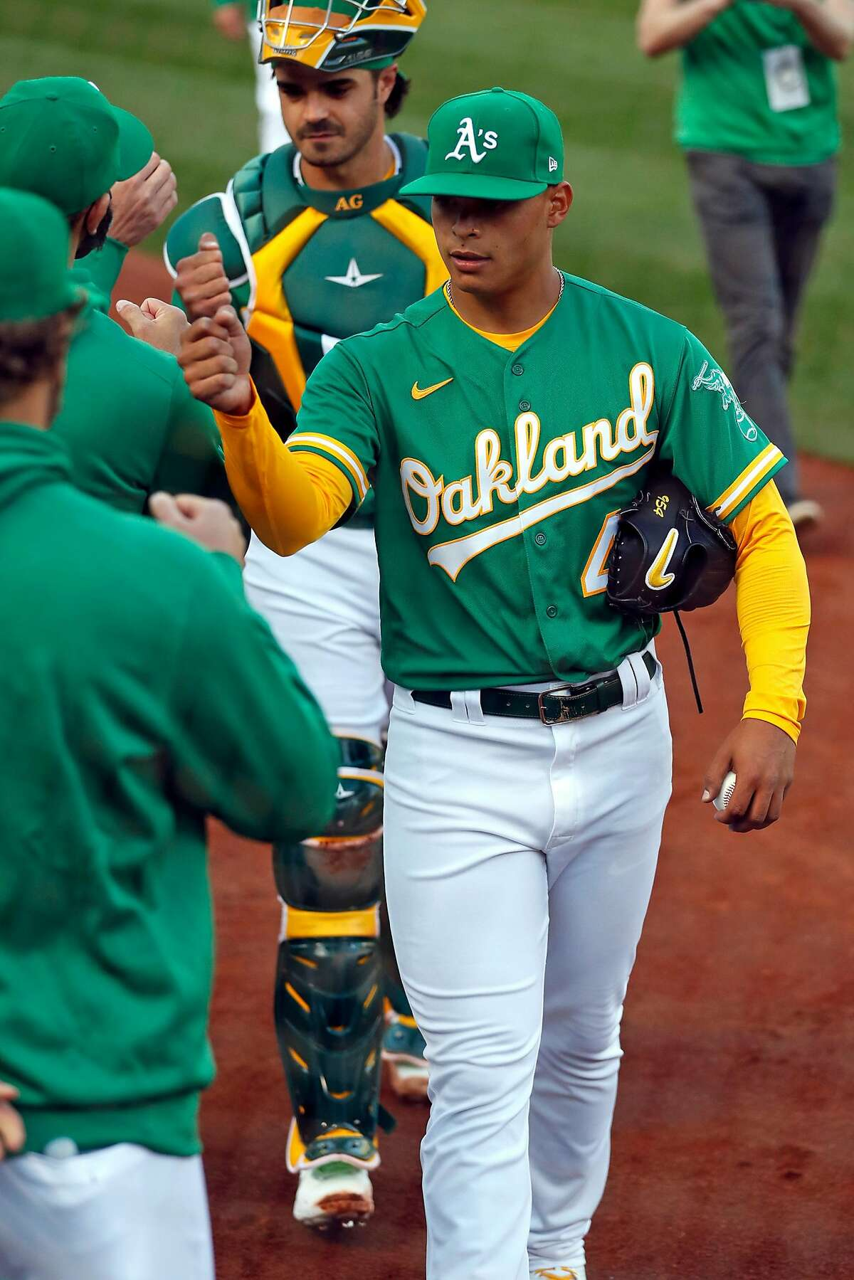 Oakland Athletics' Jesus Luzardo fist bumps teammates before facing Houston Astros during MLB game at Oakland Coliseum in Oakland, Calif., on Friday, April 2, 2021.