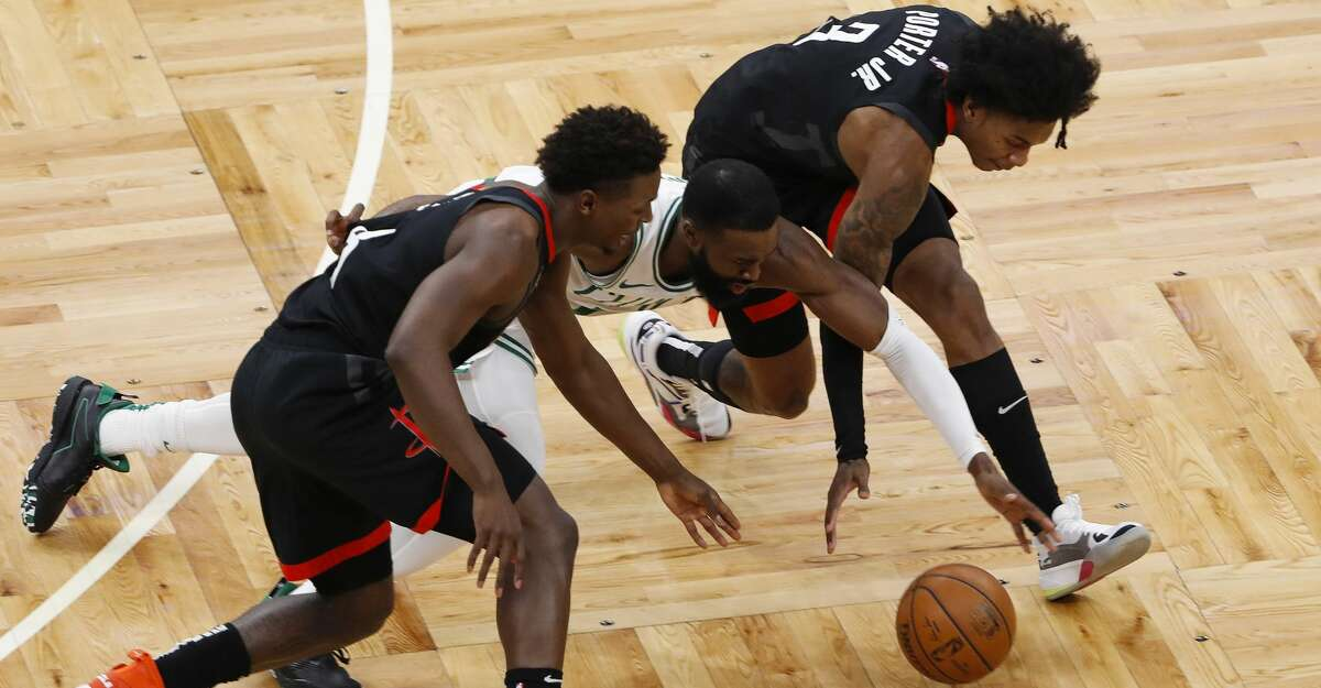Boston Celtics' Jaylen Brown reaches for a loose ball between Houston Rockets' Kevin Porter Jr., right, and Jae'Sean Tate during the second quarter of an NBA basketball game Friday, April 2, 2021, in Boston. (AP Photo/Winslow Townson)