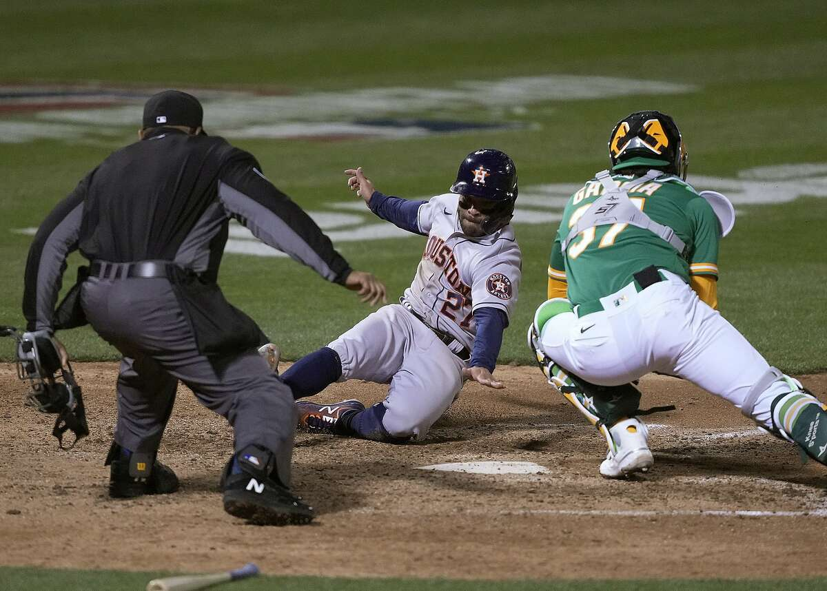 Houston Astros' Jose Altuve (27) slides into home plate to score a run past Oakland Athletics catcher Aramis Garcia (37) during the seventh inning of a baseball game Friday, April 2, 2021, in Oakland, Calif. (AP Photo/Tony Avelar)