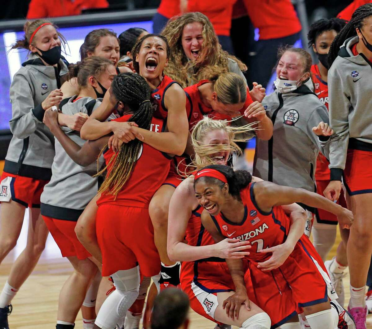 Arizona guard Aari McDonald (2) jumps in into the arms of Arizona forward Cate Reese (25) as the team celebrates their win over UConn 69-59 on Friday, April 2, 2021 at the Alamodome.
