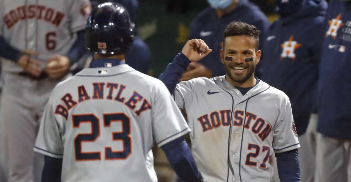 Houston Astros' Jose Altuve greets Michael Brantley after the scored on Kyle Tucker's single in 9th inning against Oakland Athletics during MLB game at Oakland Coliseum in Oakland, Calif., on Friday, April 2, 2021.