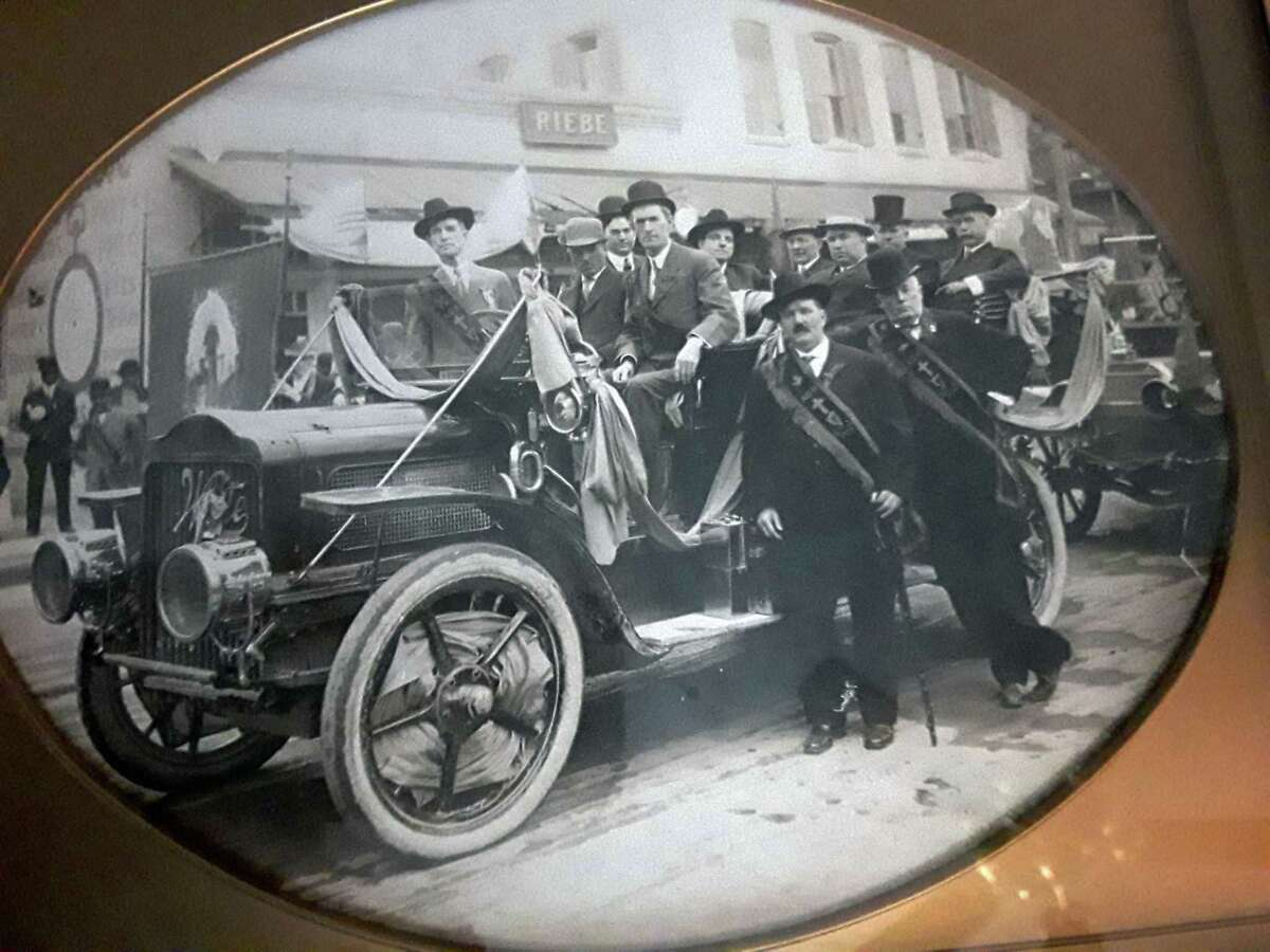 Clean-shaven Gilbert Ryan O'Shaughnessy, president of the San Antonio Ancient Order of Hibernians, stands on the running board on the left side of the car wearing a sash and western-style hat in the 1908 St. Patrick's Day parade in downtown San Antonio. Next to him is his son-in-law, Matthew Cody, a chiropractor. Sitting in the driver's seat is Tom Conway, a fellow Hibernian. Other dignitaries in the vehicle include Father Quinn, pastor of St. Mary's Catholic Church, sitting in the very back seat, wearing a top hat. Next to him is Mayor Bryan Callaghan Jr. Automobiles were a popular feature in the parades.