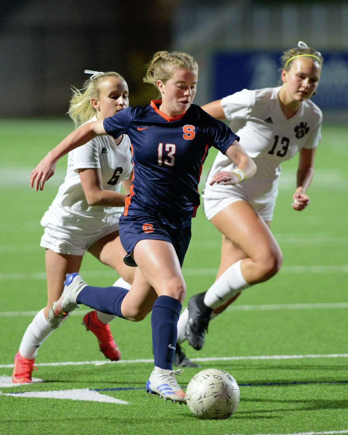 Phoebe Harpole (13) of Seven Lakes is chased by Brenley Campbell (6) and Grace Barnhart (13) of Cy-Fair during the second half of a 6A-III regional quarterfinal soccer match between the Seven Lakes Spartans and the Cy-Fair Bobcats on Friday, April 2, 2021 at Rhodes Stadium, Katy, TX.