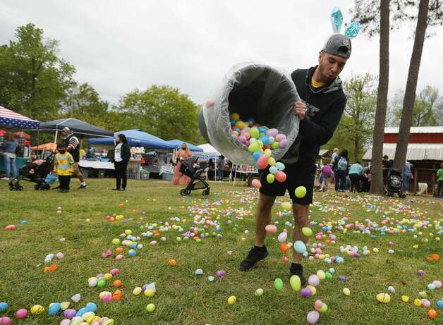 Nick Naselli dumps out more eggs for children to pick up during 7 Acre Woods'€™ annual Easter egg hunt and vendors market, Saturday, April 3, 2021, in Conroe. Photo: Jason Fochtman/Staff Photographer / 2021 © Houston Chronicle