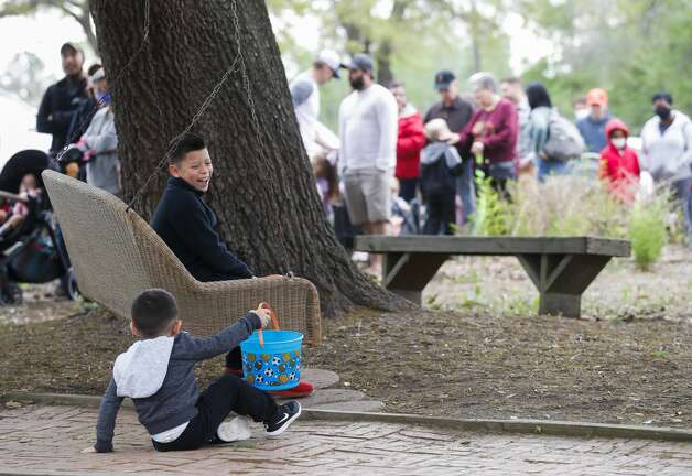 Fernando Hernandez, top, laughs after his brother, Williams, fell trying to get on the swing as their family wait in line to take part in 7 Acre Woods'€™ annual Easter egg hunt and vendors market, Saturday, April 3, 2021, in Conroe. Photo: Jason Fochtman/Staff Photographer / 2021 © Houston Chronicle