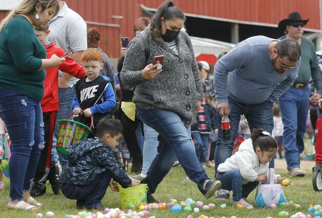 Children pick up eggs beside familiy during 7 Acre Woods annual Easter egg hunt and vendors market, Saturday, April 3, 2021, in Conroe. Photo: Jason Fochtman/Staff Photographer / 2021 ? Houston Chronicle
