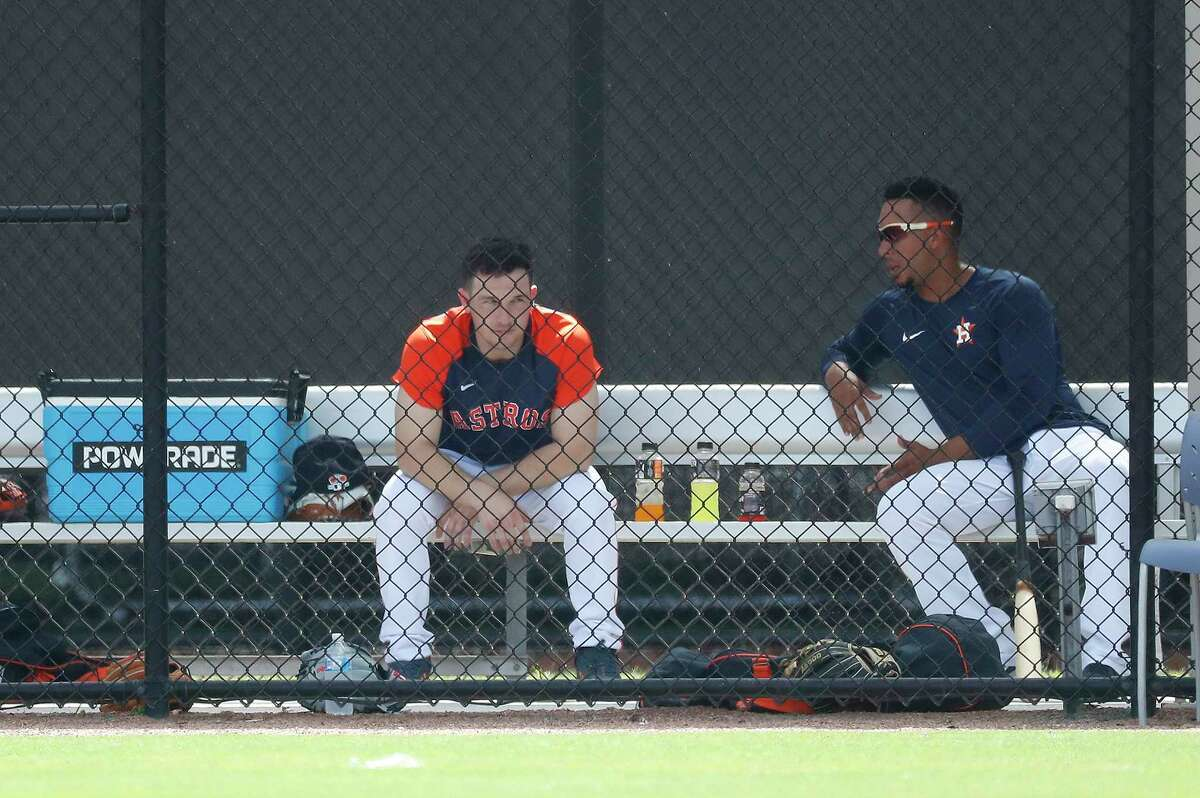 Houston Astros third baseman Alex Bregman (2) and outfielder Michael Brantley (23) take a break in the dugout during the second day of full-squad workouts for the Astros at Ballpark of the Palm Beaches in West Palm Beach, Florida, Tuesday, February 23, 2021.