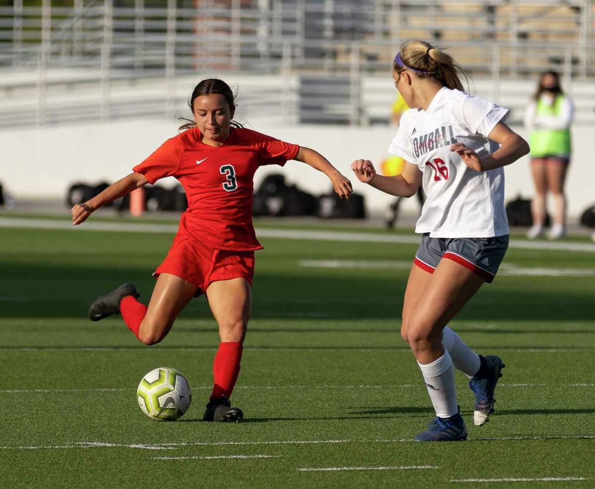The Woodlands Katherine Williams (3) kicks the ball while under pressure from Tomball defensive midfielder Brooklyn Bumgardner (16) during the first half of a Region II-6A quarterfinals soccer match at Woodforest Bank Stadium, Friday, April 2, 2021, in The Woodlands.