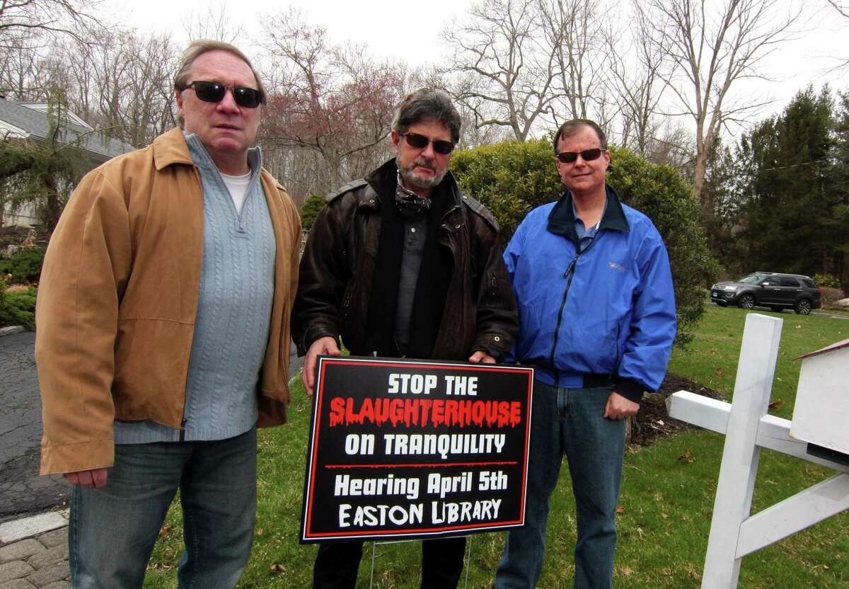 Neighbors on Tranquility Drive led by Joseph Calzone, center, are fighting a proposed commercial chicken coop and slaughterhouse in their neighborhood in Easton, Conn., on Friday April 2, 2021. Posing with Calzone is Sam Ogrodowski, left, and John Allan, right.