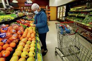 Customers including Ann Rully shop at Cranbury Market Friday, April 2, 2021, in the Cranbury neighborhood in Norwalk, Conn. The market was opened by Glen Rega in 2008. It's now the only grocery store in the neighborhood and one of small grocery stores that keeps Norwalk afloat.