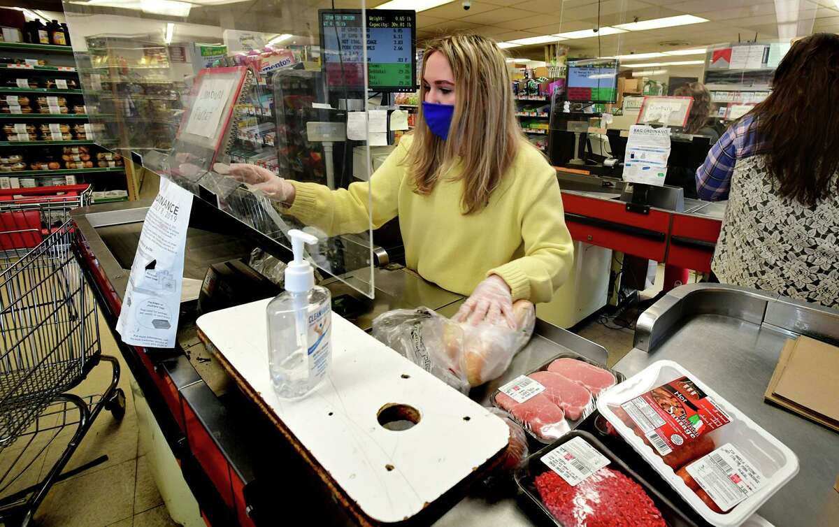 Cashier Alyssa Gayle works the register at Cranbury Market Friday, April 2, 2021, in the Cranbury neighborhood in Norwalk, Conn.