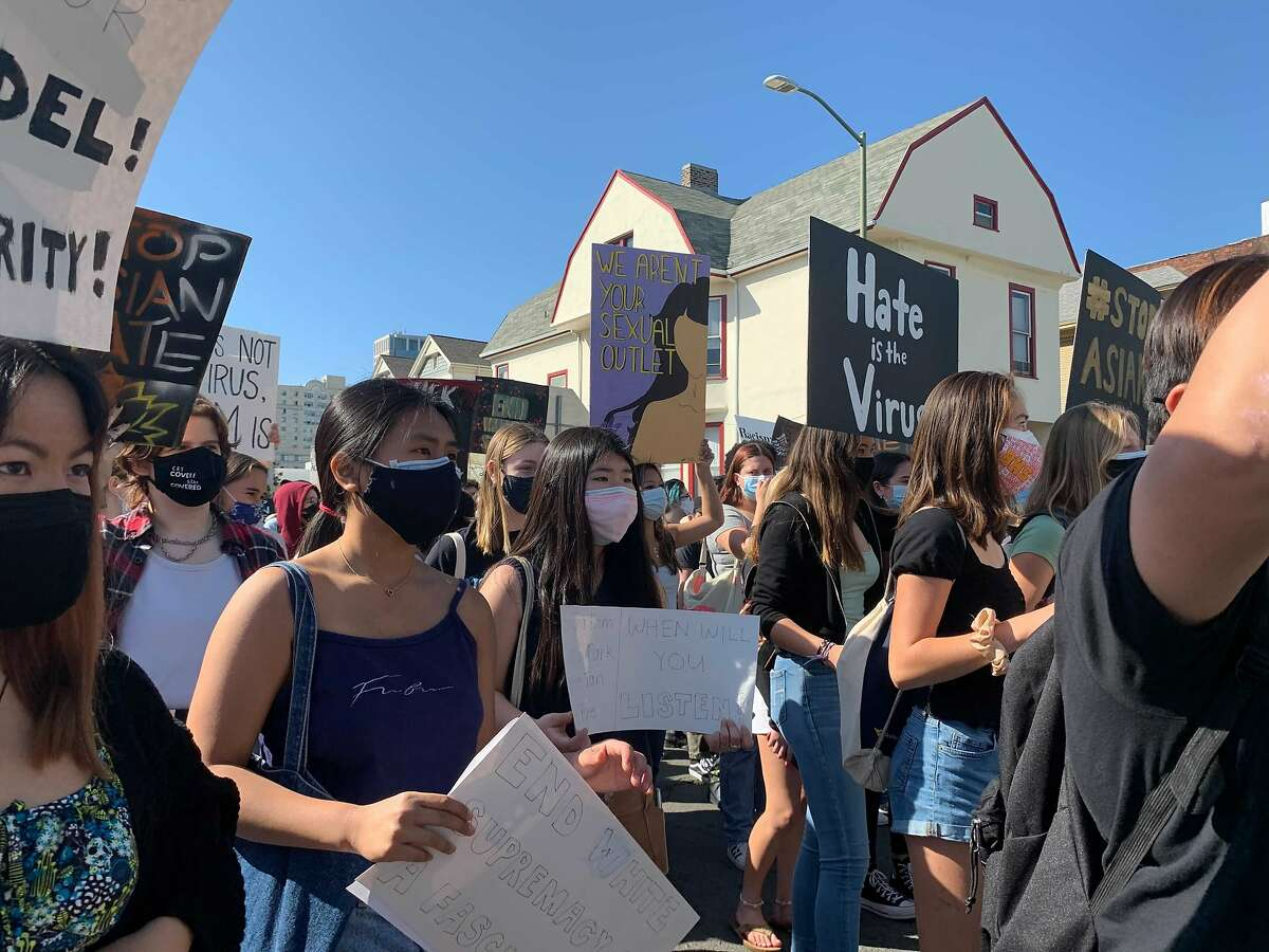 Approximately 200 marchers, most of them young, hold signs in support of the Asian American community during a youth-led rally through Oakland.