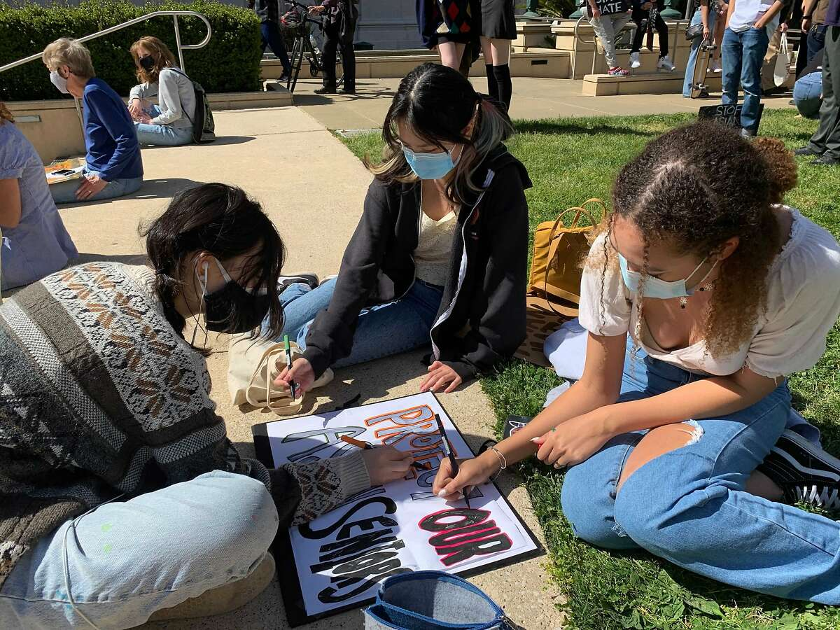 From left to right, friends Emme Birkholz, Jessica Wong and Bahia Washington, all 16, prepare a poster while waiting for a youth-led rally to start outside Oakland City Hall.