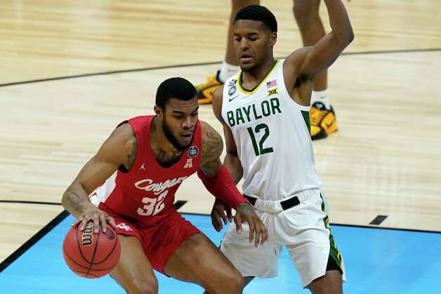Houston forward Reggie Chaney (32) drives on Baylor guard Jared Butler (12) during the first half of a men's Final Four NCAA college basketball tournament semifinal game, Saturday, April 3, 2021, at Lucas Oil Stadium in Indianapolis. (AP Photo/Darron Cummings) Photo: Darron Cummings, Associated Press / Copyright 2021 The Associated Press. All rights reserved.