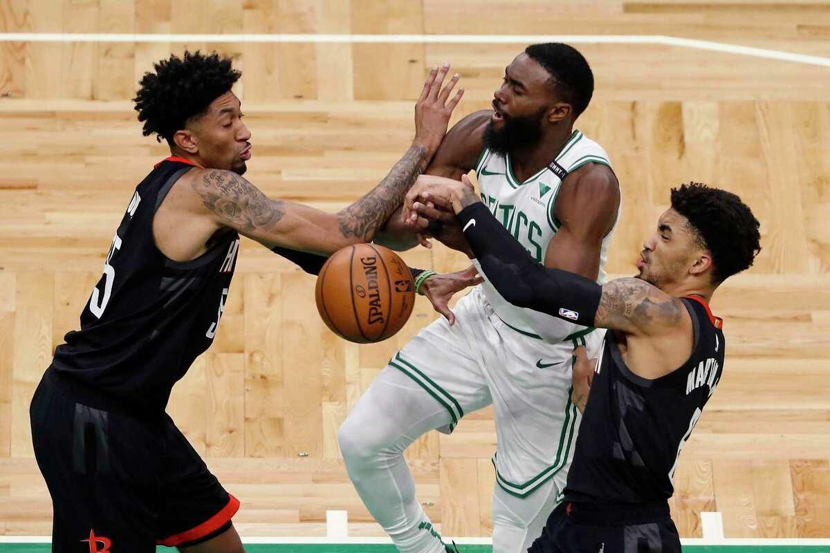 Boston Celtics' Jaylen Brown has the ball knocked away as he tries to get past Houston Rockets' Christian Wood, left, and Kenyon Martin Jr. during the second quarter of an NBA basketball game Friday, April 2, 2021, in Boston. (AP Photo/Winslow Townson)