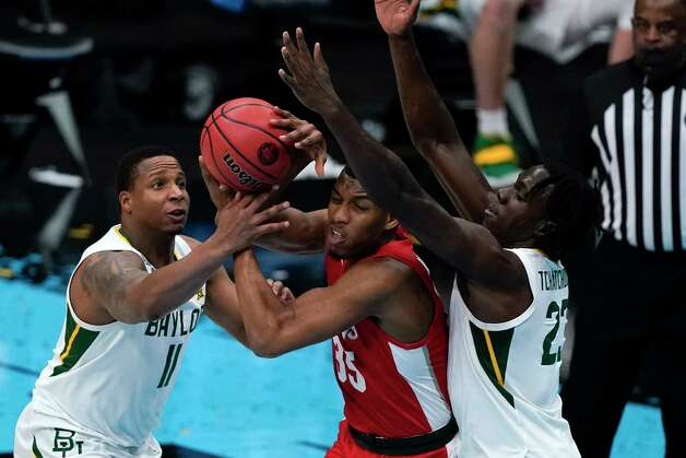Houston forward Fabian White Jr. (35) passes between Baylor guard Mark Vital (11) and forward Jonathan Tchamwa Tchatchoua, right, during the first half of a men's Final Four NCAA college basketball tournament semifinal game, Saturday, April 3, 2021, at Lucas Oil Stadium in Indianapolis. (AP Photo/Michael Conroy) Photo: Michael Conroy, Associated Press / Copyright 2021 The Associated Press. All rights reserved.