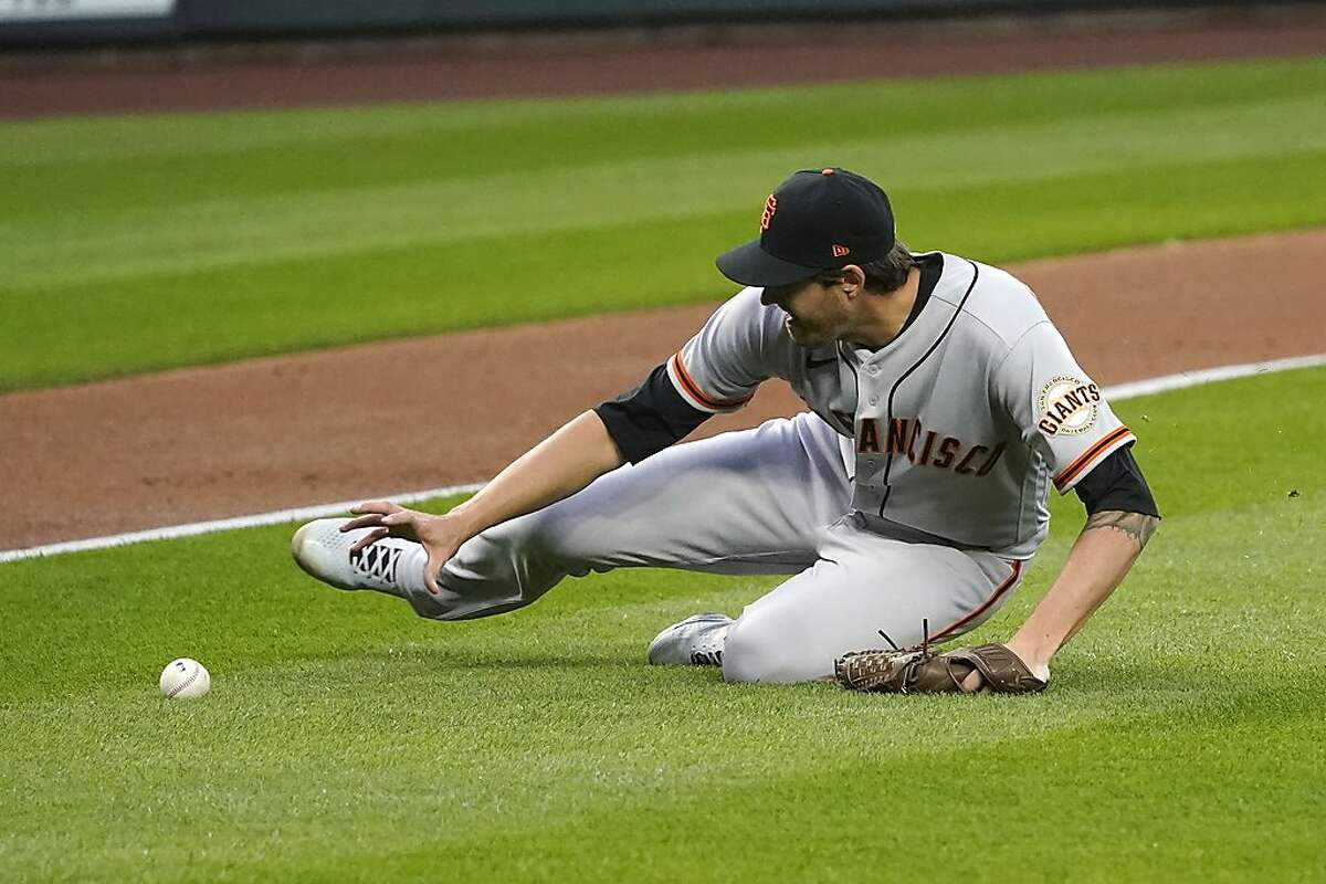 Giants starting pitcher Kevin Gausman slides across the infield to field a grounder by the Mariners' Ty France in Thursday's opener.