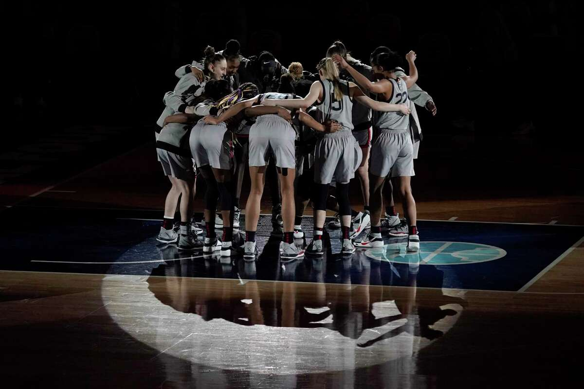 Connecticut players huddle before a women's Final Four NCAA college basketball tournament semifinal game against the Arizona Friday, April 2, 2021, at the Alamodome in San Antonio. (AP Photo/Morry Gash)
